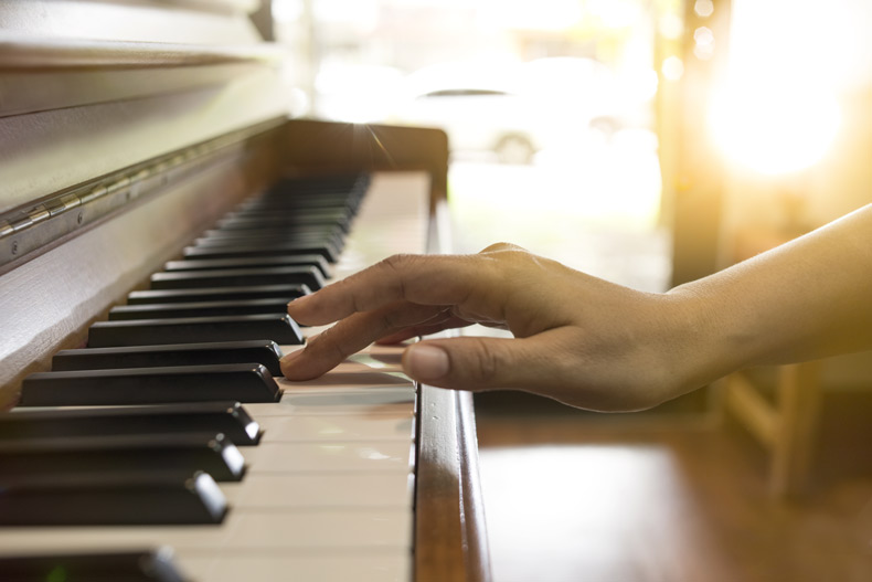 Nahaufnahme einer Hand, die ein Klavier spielt