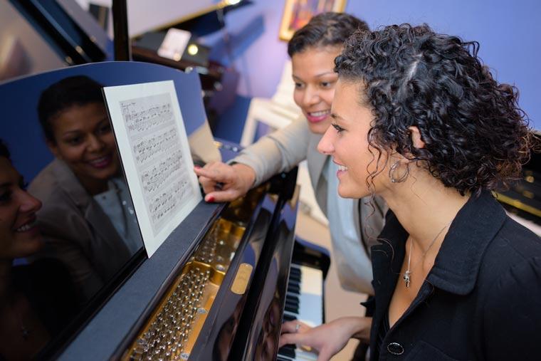 Eine Frau lernt Klavier spielen